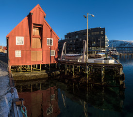 Red wooden boathouse in the docks of the harbor of Tromsø on a sunny morning, Tromsø, Norway