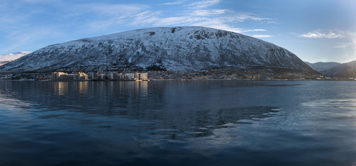 Reflections of the mountains in the ice cold water of a fjord around Tromsø, Norway