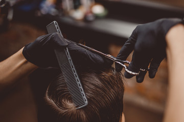 Close-up of man haircut, master does hair styling in barber shop