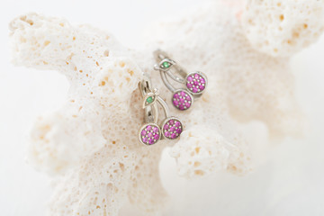 Cherry shaped earrings with pink crystals on white background