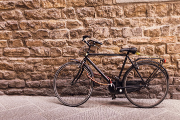 Black old bicycle against stone wall with copy space, toned.