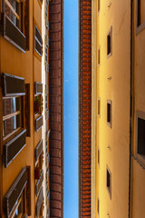 Top of the facades of narrow italian street against blue sky. Architectural abstract concept