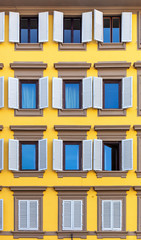 Windows with shutters on bright yellow facade