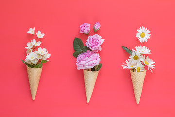 Three waffle cone with flowers bouquets on blue surface