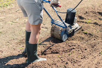 A man plows the ground in the garden with an electric cultivator