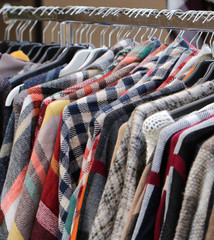 Many clothes in the hangers in a flea market