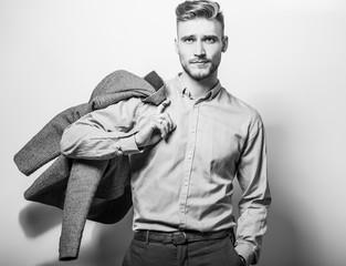 Handsome young elegant man in grey jacket pose against studio background. Black-white photo.