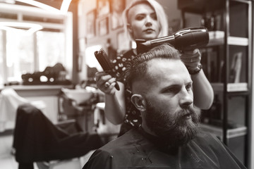 New hairstyle. Side view of young bearded man getting groomed at hairdresser with hair dryer while sitting in chair at barbershop.