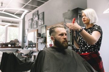The barber sprinkles on the hair of a young male client of a barber shop with water from a bulb. Haircut, styling beard.