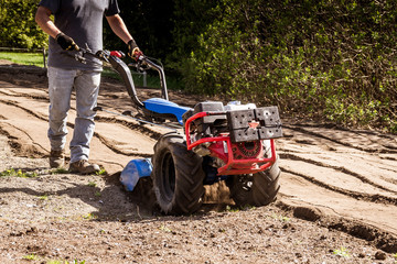 rototiller tractor unit preparing soil dirt on outdoor garden