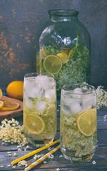 Elderberry flowers and lemon drink. Refreshing healthy summer juice. Glass of elderflower lemonade on wooden rustic board. Alternative medicine and therapy.