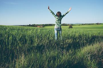 Foto auf Leinwand Olivgrun Mujer disfrutando de un día soleado en el campo con los cultivos verdes