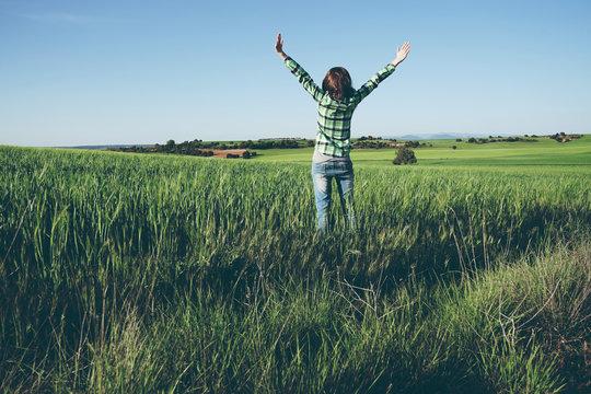 Mujer disfrutando de un día soleado en el campo con los cultivos verdes