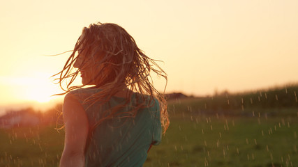 CLOSE UP: Carefree blonde woman dancing outdoors in the fresh rain at sunset.