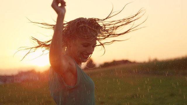CLOSE UP Joyful blonde girl enjoys her evening in countryside by dancing in rain