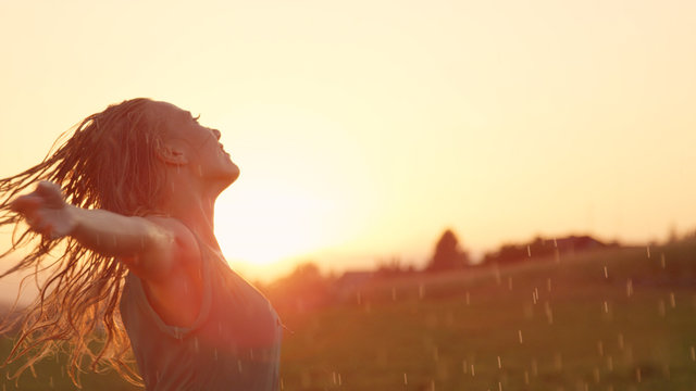 SLOW MOTION: Smiling young woman spins in the rain with her arms outstretched.