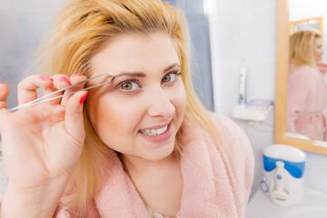 Woman tweezing eyebrows depilating with tweezers