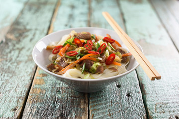 Traditional Asian noodles. Udon stir fry noodles with meat, vegetables and chili in bowl with chopsticks on rustic wooden background