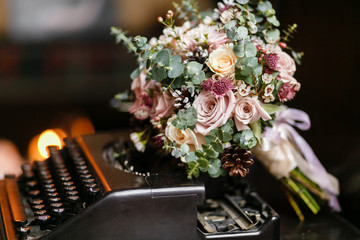 Wedding bride bouquet of fresh floral. White ranunculus flowers on typewriter,.