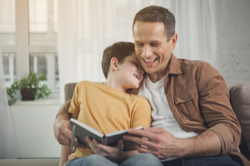 Joyful parent is embracing boy while holding a book. They are sitting on couch and smiling