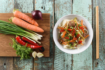 Healthy eating. Traditional Asian udon noodles and raw ingredients: onion, carrot, spring onion, chili and garlic on rustic blue background