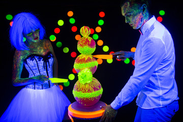Neon photography bright colorful on a dark background in ultraviolet rays, couple in love guy and girl bride with groom at a wedding cut wedding cake UV radiation