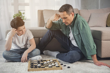 Pensive father and son are playing checkers together in living room. They are looking at board and thinking