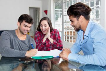 Junges Paar unterschreibt Vertrag bei Makler