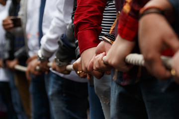 Various people pulling rope together, closeup of hands. Teamwork. Unity concept. Selective focus