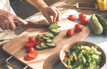 Close up of old female hands cutting vegetables on wooden board. Woman is wearing earphones while listening to music from smartphone playlist