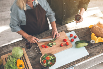 Top view of cheerful mature couple standing in kitchen. Woman is cutting vegetables while man is holding a wineglass. Focus on healthy food on table
