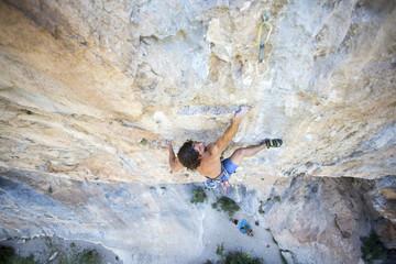 Man climbing rock wall, Pobla de Segur, Lleida, Spain