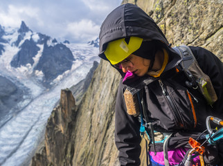 Female rock climber looking down in French Alps, Aiguille du Grepon, Haute-Savoie, France