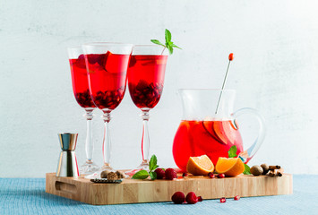 fresh summer red sangria from ripe fruits and berries, as well as wine on the table in glasses and a decanter. spices and mint leaves