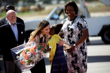 Spain's Queen Letizia Ortiz is greeted by a girl who gives her a floral bouquet in presence of Haiti's first lady Martine Moise during her arrival to Port-au-Prince