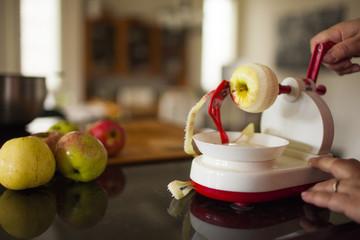 Person peeling apples with apple peeler