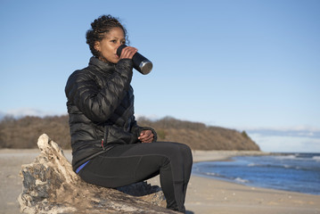 Woman drinking coffee from thermos at beach