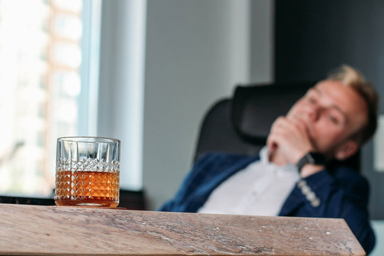 alcohol in the workplace. the businessman is resting after work.