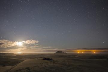 Hiker in sleeping bag on top of sand dune at sunset, Oregon Dunes National Recreation Area, Oregon, USA