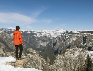 Female hiker looking at view of Yosemite National Park from Taft Point in winter with Half Dome visible, California, USA
