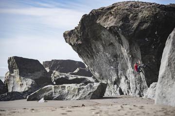 Woman bouldering on beach, Klamath, California, USA