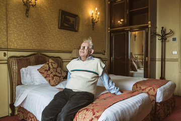 Senior sitting on hotel bed, Alexandria, Egypt