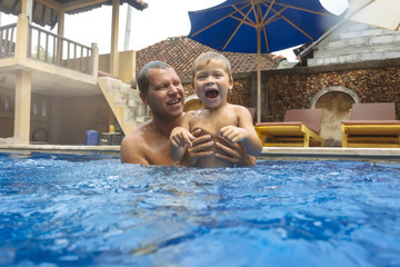 Father and son in swimming pool,Bali,Indonesia