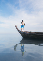A man stands on the bow of a Thai longboat