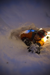Boy digging hole in snow