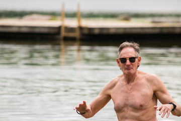 Old topless senior citizen baby boomer man standing in smooth beautiful lake with a wooden dock in the background