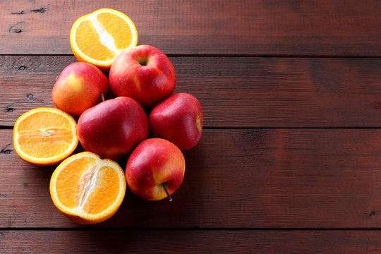 Fruits of oranges and red apples on a dark brown wooden background, halves of oranges on wooden boards. Citrus fruits and apples for vegetarian breakfast