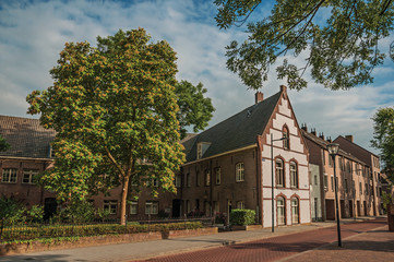 Empty street with large brick house, trees in a garden surrounded by fence and blue sky at sunset in s-Hertogenbosch. Gracious historical city with vibrant cultural life. Southern Netherlands.