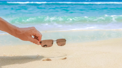 Commercial summer background, hand holding the product - sunglasses from sandy beach on blue ocean background