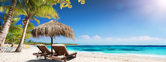 Zelfklevend Fotobehang Strand Caribbean Palm Beach With Wooden Chairs And Straw Umbrella - Idyllic Island